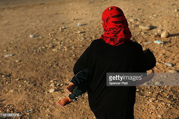 An Iraqi woman walks with her child outside of a displacement camp for those caughtup in the fighting in and around the city of Mosul on June 28 2014...