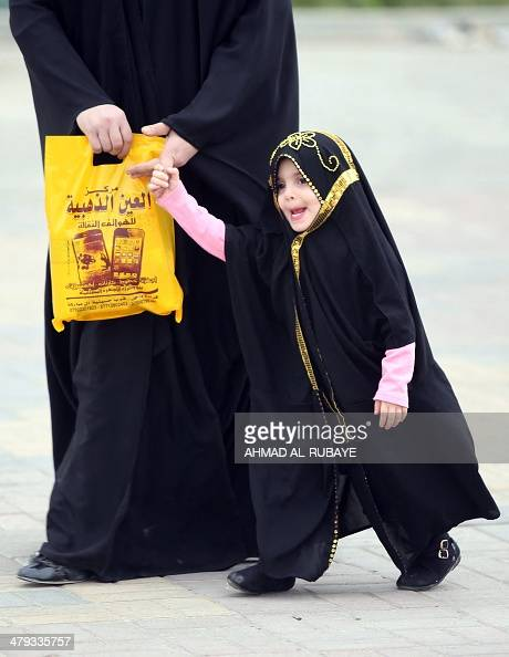 An Iraqi woman walks with her fully veiled daughter in Baghdad on March 18 2014 A bill before Iraq's parliament that opponents say legalises child...
