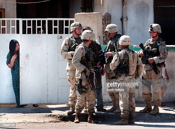 An Iraqi woman watches a group of US Army soldiers from inside her front gate while standing guard near a local protest against the detention of...