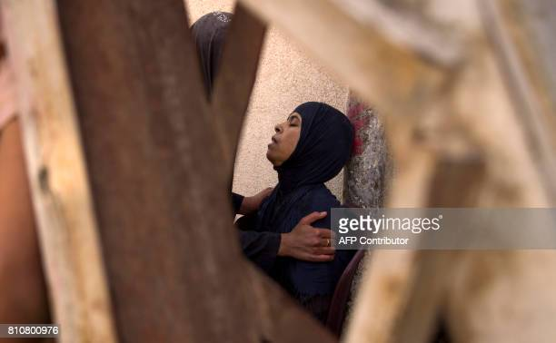 An Iraqi woman who fled the fighting between government forces and Islamic State group jihadists in the Old City of Mosul sits while being comforted...