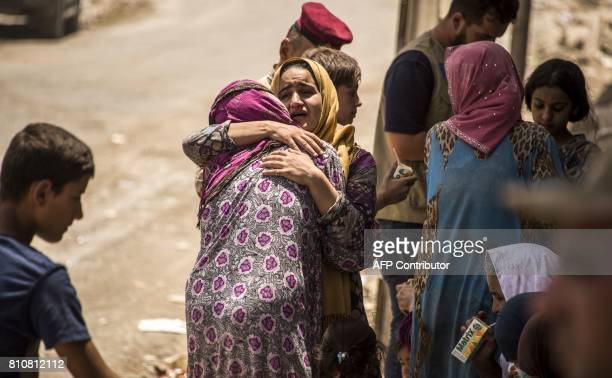 An Iraqi woman who fled the fighting between government forces and Islamic State group jihadists in the Old City of Mosul reacts while embracing...