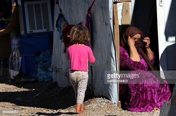 An Iraqi woman who fled the violence in the northern city of Tal Afar covers her face at the Bahrka camp for internally displaced people some ten...