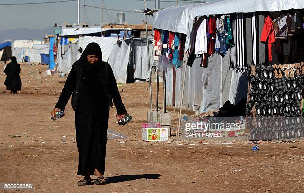 An Iraqi woman who fled violence in the northern city of Tal Afar walks through the Bahrka camp for internally displaced people some ten kilometres...