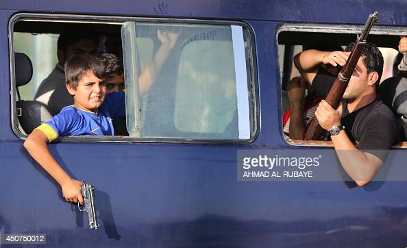An Iraqi young boy holds a gun from the window of a vehicle carrying volunteers joining Iraqi security forces in the fight against Jihadist militants...