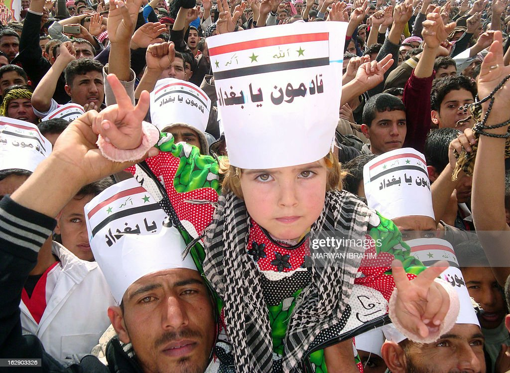 An Iraqi young boy, whose head is covered with a placard reading 'Baghdad we are coming', flashes the sign of victory during a rallye following the Friday's prayers to call for the government's fall on March 1, 2013 in Hawijah near the ethnically mixed city of Kirkuk. Protests have been staged in Sunni-majority areas of Iraq in recent weeks, calling for the resignation of Prime Minister Nuri al-Maliki and decrying the alleged targeting of their community by the Shiite-led authorities.