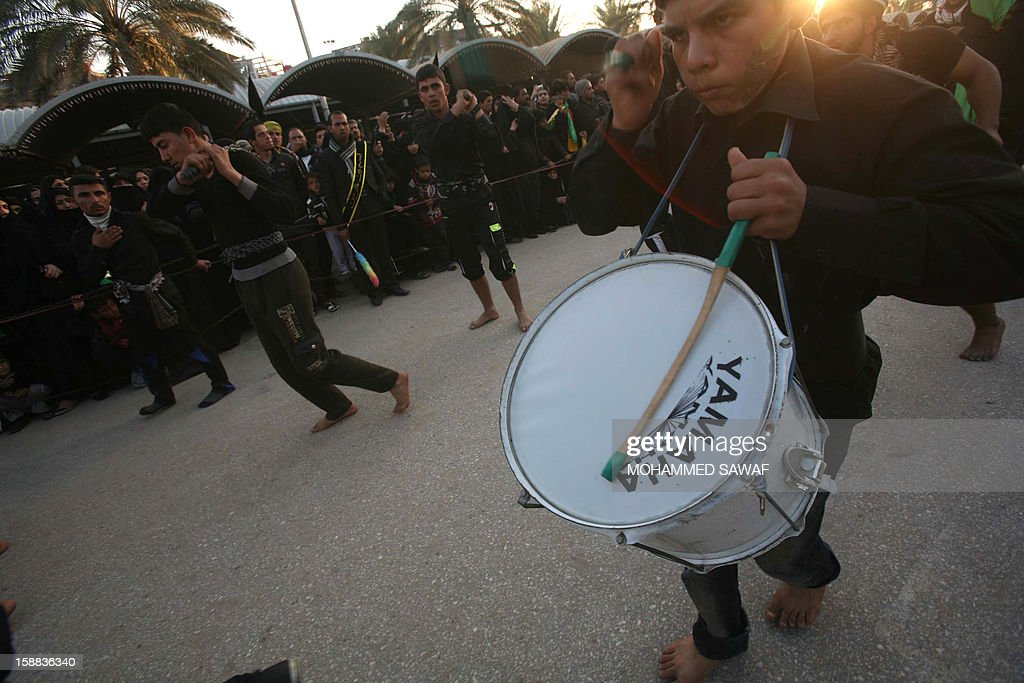An Iraqi youth drums as Iraqis take part in the Arbaeen religious festival which marks the 40th day after Ashura commemorating the seventh century killing of Prophet Mohammed's grandson, Imam Hussein, in the shrine city of Karbala, southwest of Iraq's capital Baghdad, on December 31, 2012. A wave of bombings and shootings killed 12 people as Iraq grappled with anti-government protests and simmering political crises ahead of major Shiite Muslim commemoration rituals.