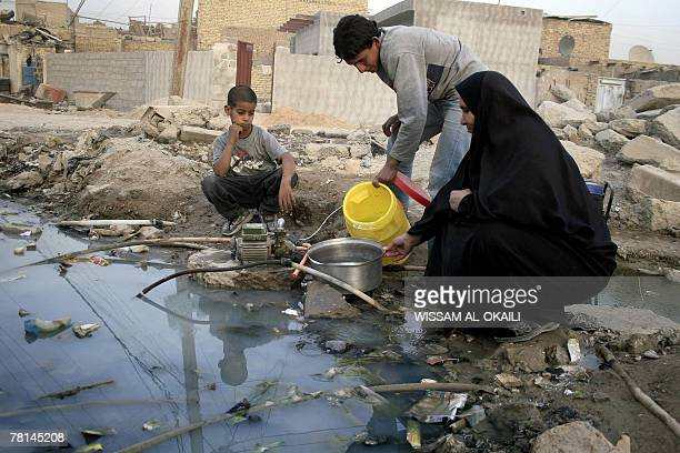 An Iraqi youth fills a pan with drinking water that he got from a burst water pipe on the outskirts of the impoverished Baghdad district of Sadr City...