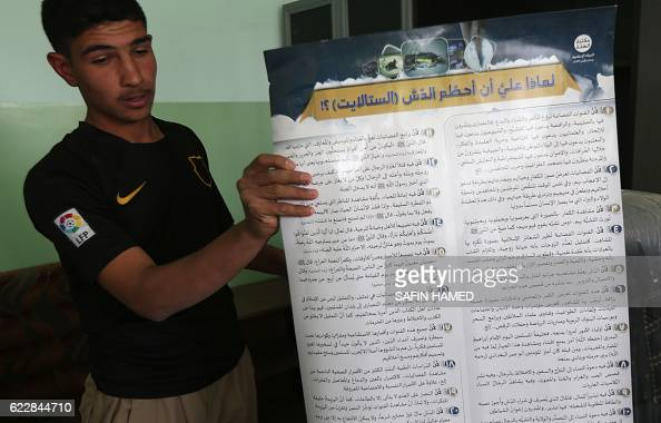 An Iraqi youth shows a placard printed out by the Islamic State group explaining why people shouldn't use satellite dishes as he visits his school in...