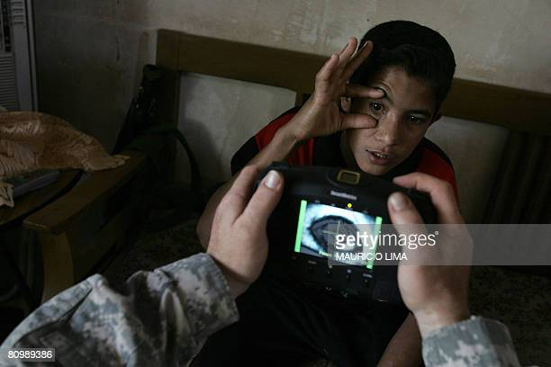 An Iraqi youth who presented himself as a 17yearold stretches his eye as a US soldier scans his iris using a biometrics digital system camera during...