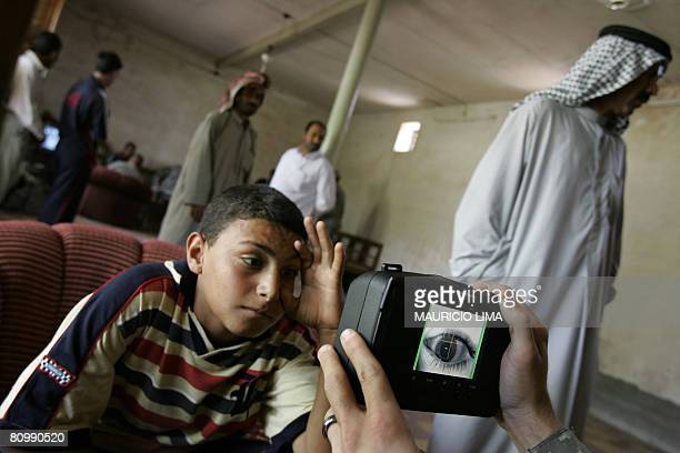 An Iraqi youth who presented himself as an 18yearold stretches his eye as a US soldier scans his iris using a biometrics digital system camera during...