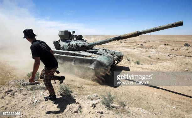 TOPSHOT An Iraqimodified T72M tank belonging to the progovernment Hashed alShaabi paramilitary forces advances towards the UNESCOlisted ancient city...