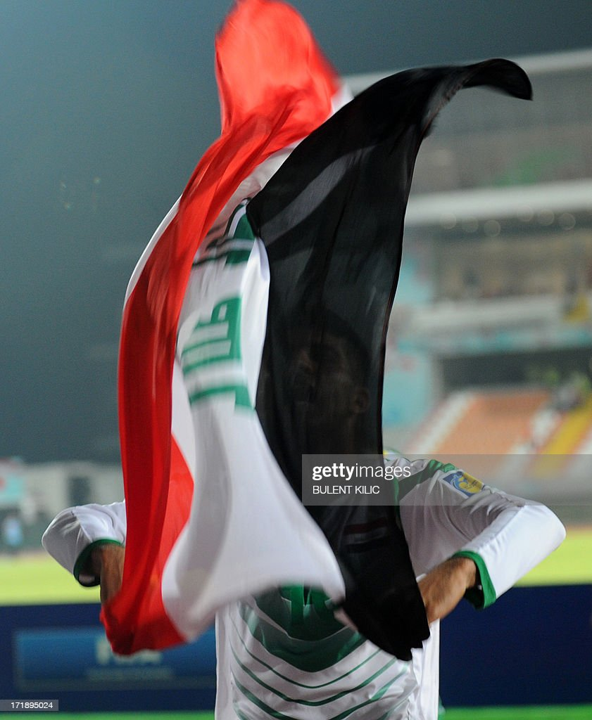 An Iraq's player waves the national flag after the victory of his team during a group stage football match between Iraq and Chile at the FIFA Under 20 World Cup at Akdeniz University Stadium in Antalya on June 29, 2013.