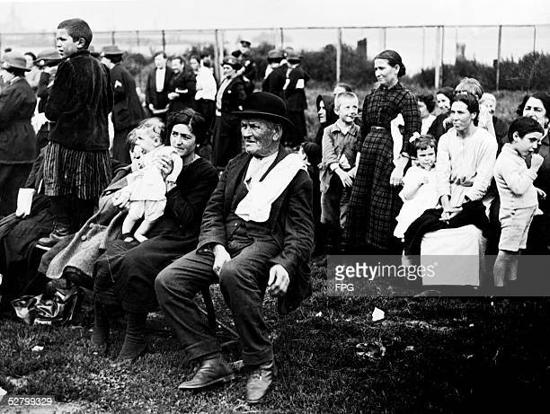An Irish immigrant sits on a chair and waits next to an Italian immigrant and her children Ellis Island early 20th Century