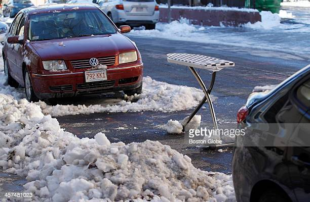 An ironing board is used as a space saver to claim a shoveled parking spot on East 4th Street in South Boston Massachusetts on December 16 after the...