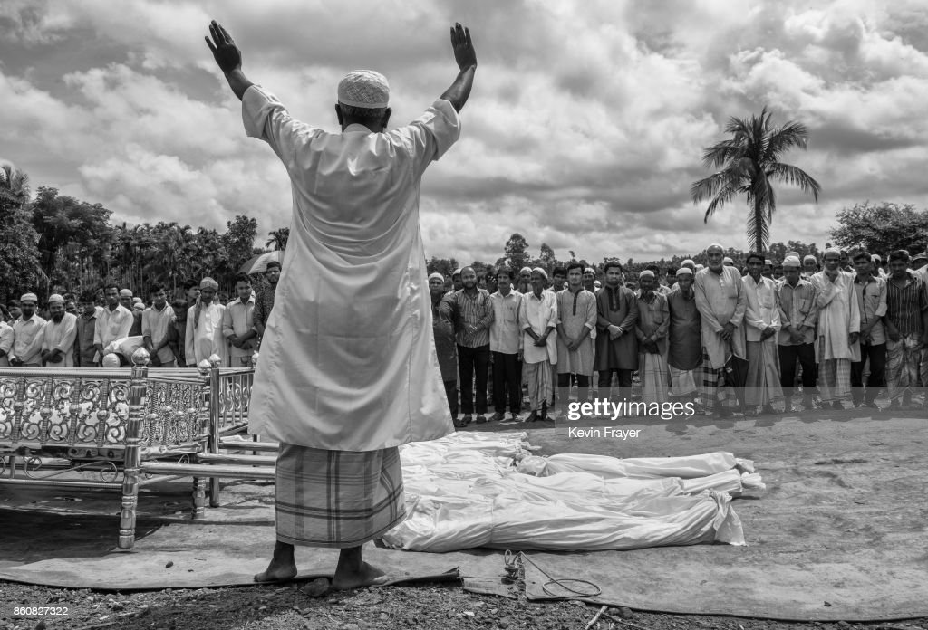 COX'S BAZAR, BANGLADESH - SEPTEMBER 29: An Islamic cleric leads prayers for 16 Rohingya refugees who dies when their boat capsized while fleeing Myanmar during their funeral on September 29, 2017 in Cox's Bazar, Bangladesh. More than half a million Rohingya refugees have flooded into Bangladesh to flee an offensive by Myanmar's military that the United Nations has called 'a textbook example of ethnic cleansing'. The refugee population is expected to swell further, with thousands more Rohingya Muslims said to be making the perilous journey on foot toward the border, or paying smugglers to take them across by water in wooden boats. Hundreds are known to have died trying to escape, and survivors arrive with horrifying accounts of villages burned, women raped, and scores killed in the 'clearance operations' by Myanmar's army and Buddhist mobs that were sparked by militant attacks on security posts in Rakhine state on August 25, 2017. What the Rohingya refugees flee to is a different kind of suffering in sprawling makeshift camps rife with fears of malnutrition, cholera, and other diseases. Aid organizations are struggling to keep pace with the scale of need and the staggering number of them - an estimated 60 percent - who are children arriving alone. Bangladesh, whose acceptance of the refugees has been praised by humanitarian officials for saving lives, has urged the creation of an internationally-recognized 'safe zone' where refugees can return, though Rohingya Muslims have long been persecuted in predominantly Buddhist Myanmar. World leaders are still debating how to confront the country and its de facto leader, Aung San Suu Kyi, a Nobel Peace Prize laureate who championed democracy, but now appears unable or unwilling to stop the army's brutal crackdown.