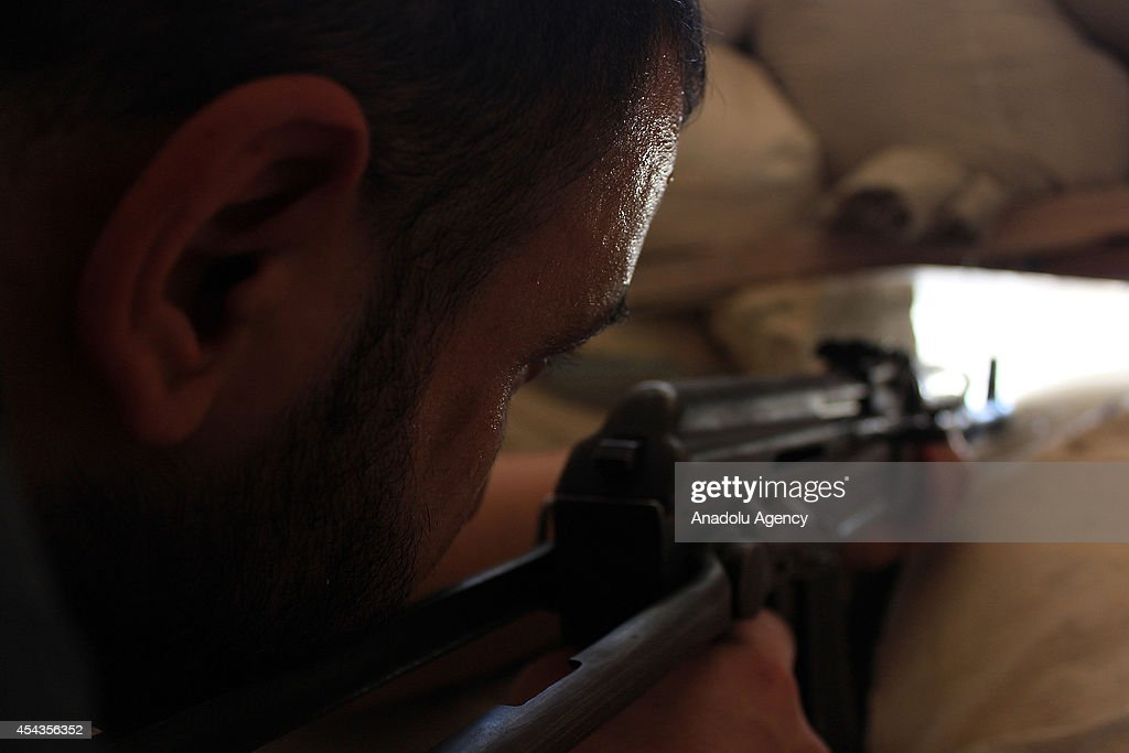 An Islamic Front member aims at the Syrian regime's snipers deployed in the municipality building damaged during the clashes in Aleppo, Syria on August 29, 2014.