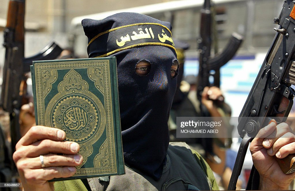 An Islamic Jihad militant holds up a copy of the Koran in one hand and an automatic rifle in the other during a rally in Beit Lahia in the northern Gaza Strip, 10 June 2005. Hundreds of Palestinians have been protesting in various towns and cities in the occupied territories after allegations that Israeli police desecrated copies of the Koran during searches of prison cells, claims which have been vehemently denied by Israel. AFP PHOTO/MOHAMMED ABED