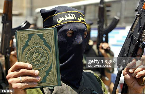 An Islamic Jihad militant holds up a copy of the Koran in one hand and an automatic rifle in the other during a rally in Beit Lahia in the northern...