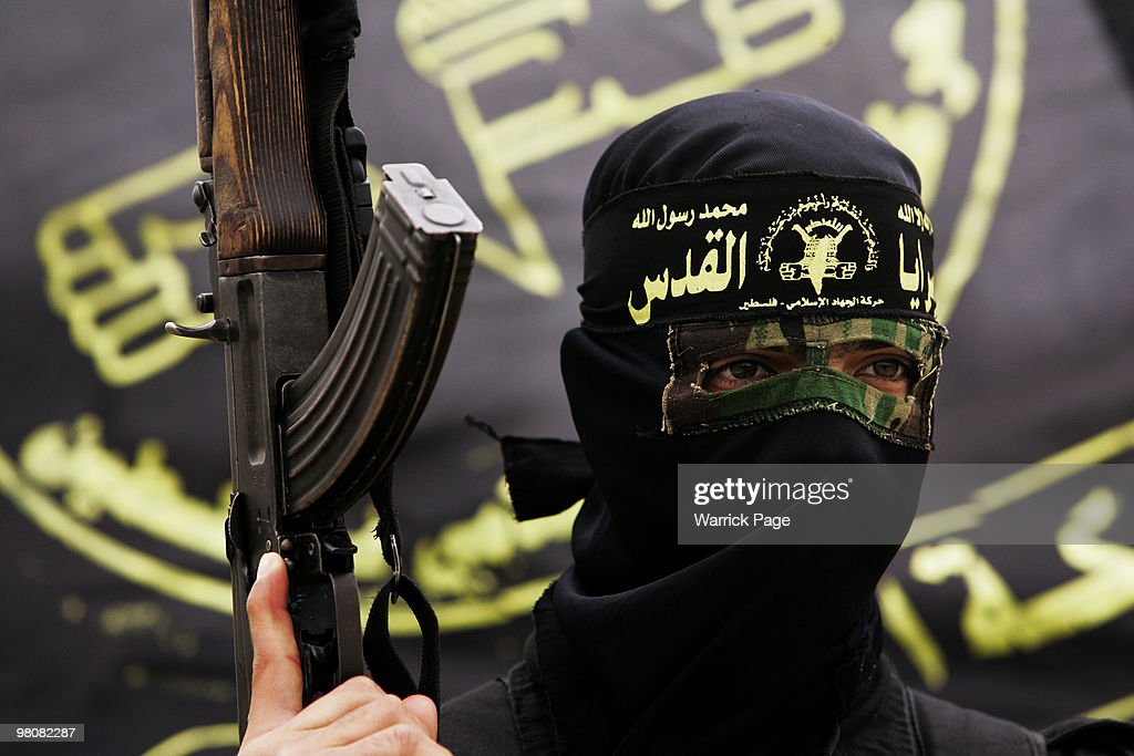 An Islamic Jihad militant stands on top of a mosque during the funeral of Haithem Arafat who was killed on Friday in clashes with Israeli soldiers on...