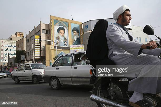 An Islamic Mullah and his wife ride past portraits of the late Ayatollah Khomeini and Iran's current supreme leader Ayatollah Khamenei on June 3 2014...