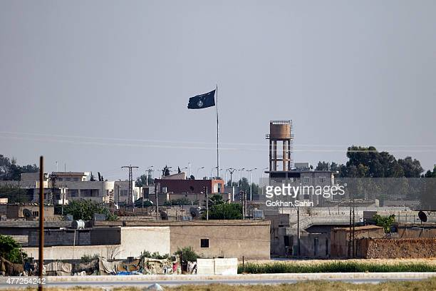 An Islamic State flag flies in the northern Syrian town of Tel Abyad as it is pictured from the Turkish border town of Akcakale in Sanliurfa province...