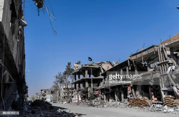 An Islamic State group flag flutters above heavily damaged buildings in Raqa on October 21 after a Kurdishled force expelled the jihadists from the...