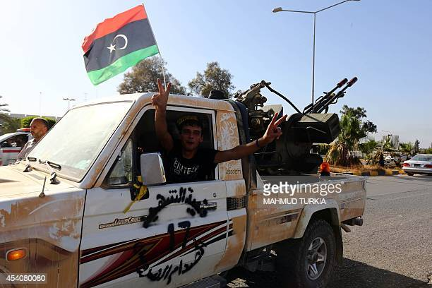 An Islamist fighter from the Fajr Libya coalition flashes the V sign for victory at the entrance of Tripoli international airport on August 24 after...