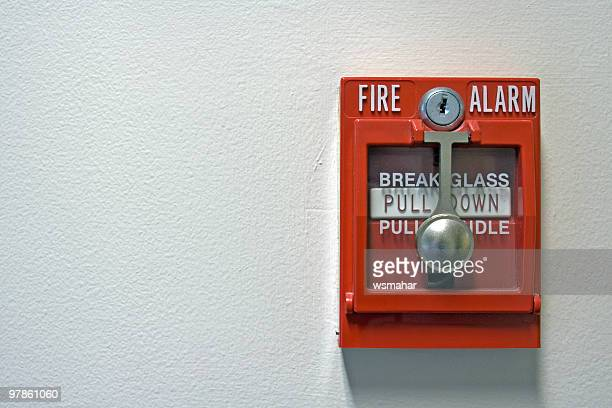 An isolated red fire alarm on a wall