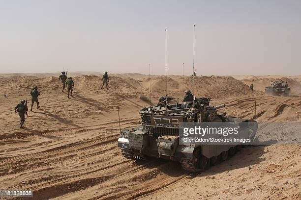 An Israel Defense Force Merkava Mark II main battle tank working closely with infantry forces.