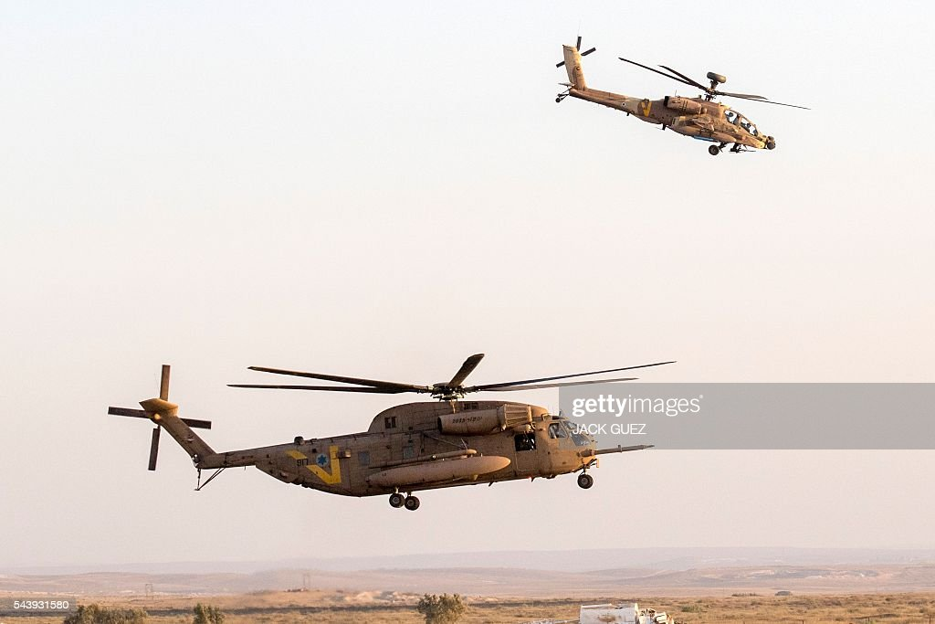 An Israeli AH-64 Apache Longbow helicopter (R) and a Sikorsky CH-53K helicopter take part in an air show at the graduation ceremony of Israeli air force pilots on June 30, 2016, at the Hatzerim base in the Negev desert, near the southern Israeli city of Beer Sheva. / AFP / JACK