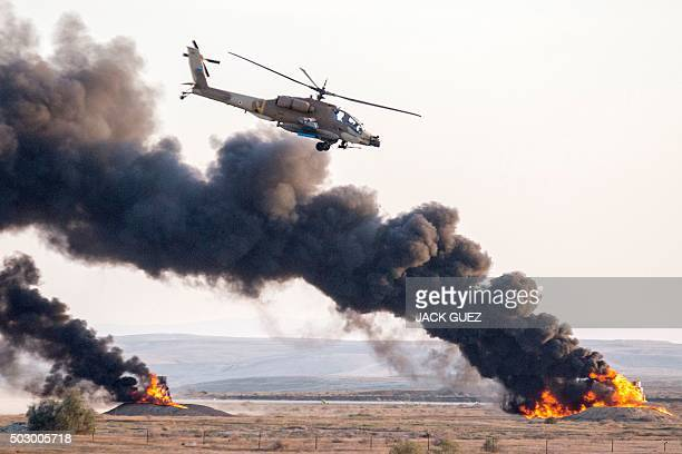 An Israeli AH64 Apache longbow helicopter takes part in an air show for a graduation ceremony at the Hatzerim base in the Negev desert near the...