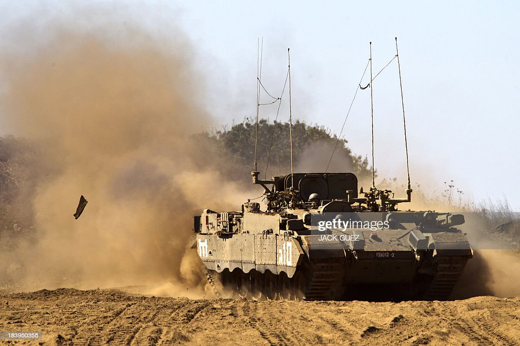 An Israeli army Armoured Personnel Carrier (APC) rolls in a training field in the Golan Heights, next to the Israeli-Syrian border, on October 10, 2013. The Israeli army fired on October 9, a Tammuz missile across the Syrian border in response to mortar fire from the Syrian at an Israeli military base in the northern Israeli-annexed Golan Heights leaving two soldiers with light wounds. AFP PHOTO / JACK GUEZ