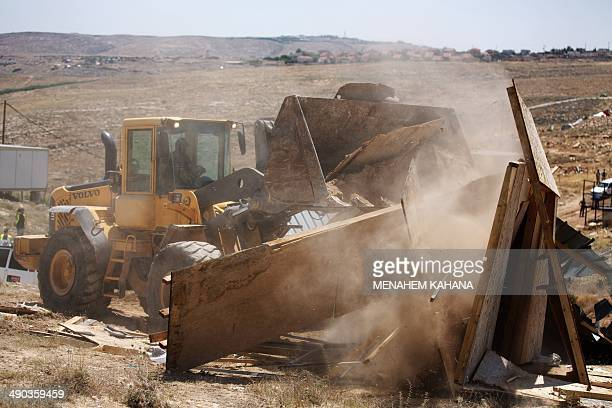 An Israeli army bulldozer demolishes an illegal house in the West Bank settlement of Maale Rehavam southeast of Bethlehem on May 14 2014 Israeli...