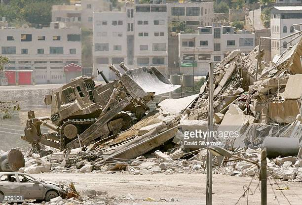 An Israeli army bulldozer searches the ruins of the Palestinian police building June 30 2002 in the West Bank town of Hebron The army is looking for...