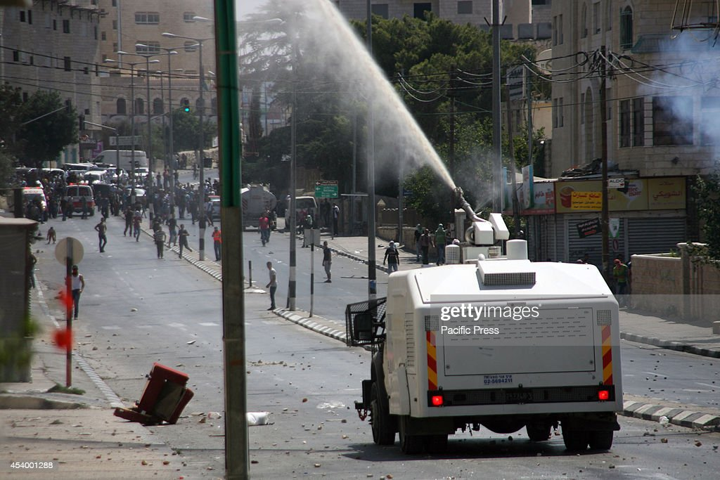 An Israeli army jeep sprays foul smelling water dubbed, 'skunk water' at the civilian Palestinian protesters. The Palestinian youths organized protest in solidarity with Gaza, in the West Bank city of Bethlehem. After the truce talks in Cairo this week completely failed, a renewed violent war started on Wednesday. The heavy exchange of missiles from the fighting countries caused death of the Hamas senior leaders, increased death toll of innocent people, and devastated wide arrays of properties. To date, the war death toll reached to 2,090 Palestinians and 67 Israelis.