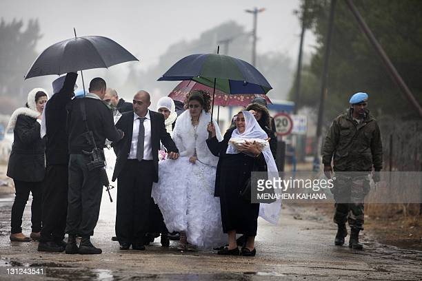 An Israeli army officer welcomes Mayanda Abud a 27yearold Syrian Druze bride from Damascus and her 30yearold groom Munjed Awad as they cross the...
