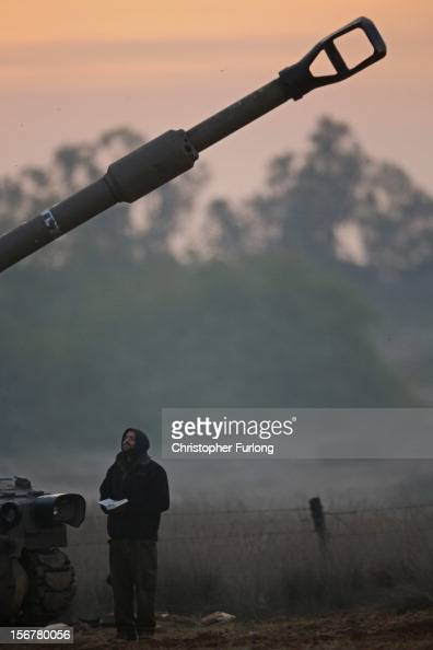 An Israeli artillery gunner prays at sunrise next to his 155mm cannon at an emplacement on November 21 2012 on Israel's border with the Gaza Strip...