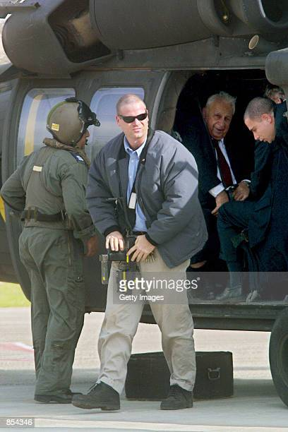 An Israeli bodyguard armed with an Uzi submachine gun guards Israeli Prime Minister Ariel Sharon in an airforce helicopter in Jerusalem November 27...
