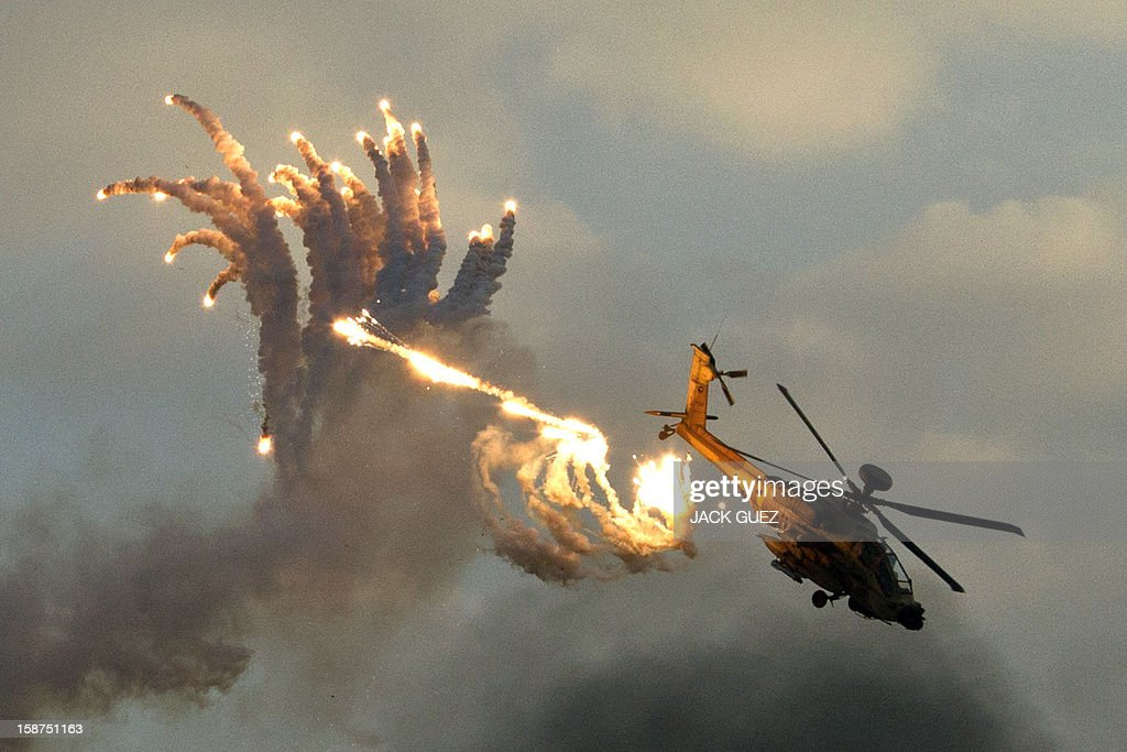 An Israeli Boeing AH-64 Apache longbow helicopter launches anti-missile flares during an air show at the graduation ceremony of Israeli pilots at the Hatzerim air force base in the Negev desert, near the southern Israeli city of Beersheva on December 27, 2012. AFP PHOTO / JACK GUEZ
