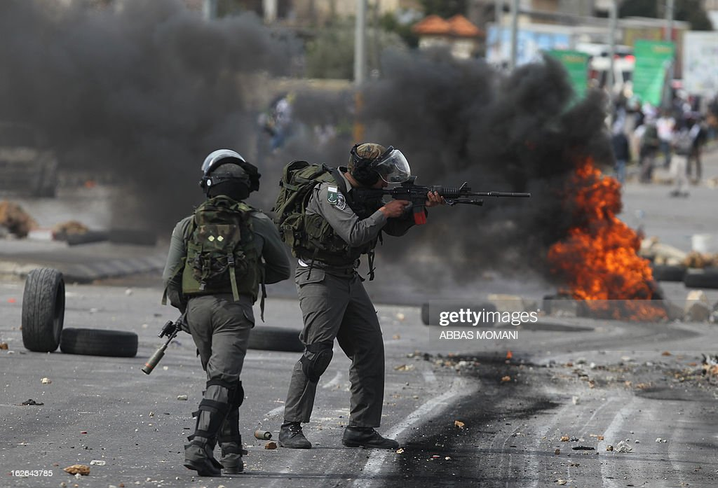 An Israeli border guard aims a weapon during clashes with Palestinian youths outside Israel's Ofer prison near Ramallah on February 25, 2013 after a protest in support of Palestinian prisoners on hunger strike in Israeli prisons. Palestinian president Mahmud Abbas said that Israel was deliberately seeking to stoke unrest in the occupied West Bank but that Palestinians would not be provoked. AFP PHOTO/ABBAS MOMANI