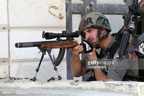 An Israeli border guard aims his sniper rifle during clashes with Palestinian protesters following an antiIsraeli protest after the weekly Friday...