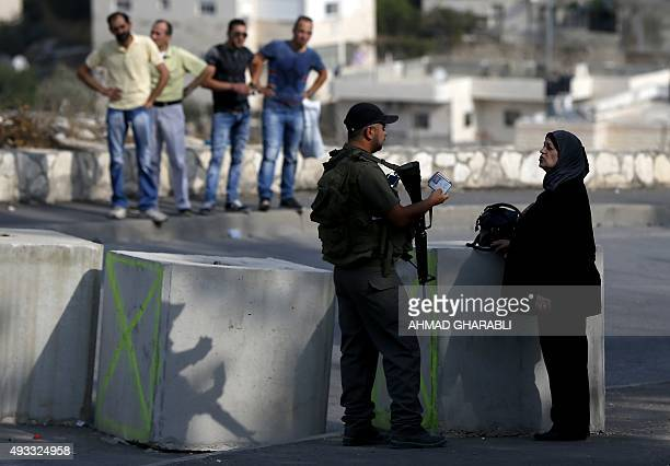 An Israeli border guard checks the ID of a Palestinian woman at a newly erected checkpoint at the exit of the east Jerusalem neighborhood of Issawiya...