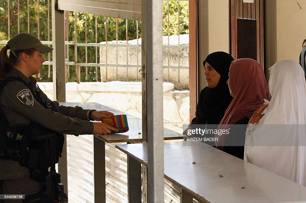 An Israeli border guard checks the identification cards of Palestinian Muslim women heading to pray at a religious site known to Muslims as the Ibrahimi Mosque and to Jews as the Cave of the Patriarchs, at a checkpoint in the flashpoint city of Hebron, in the occupied West Bank, on July 1, 2016. A Palestinian woman attempted to stab an Israeli guard at a flashpoint West Bank shrine and was shot dead, Israeli police said, the third violent incident in two days. BADER