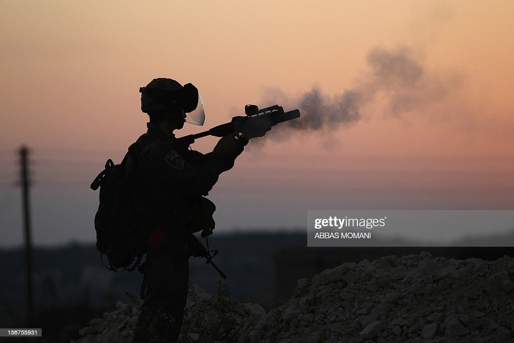 An Israeli border guard fires a tear gas canister during clashes with Palestinians following the funeral of a policeman who died two days ago at a demonstration against the Israeli military offensive on the Gaza Strip, on November 20, 2012 in the West Bank village of Nabi Saleh, near Ramallah. The West Bank has witnessed almost daily demonstrations in support of Gaza Palestinians who have faced a week of Israeli air strikes against militants firing rockets at the Jewish state.
