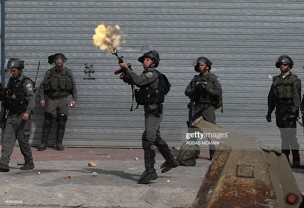 An Israeli border guard fires a tear gas cansiter during clashes with Palestinian youths outside Israel's Ofer prison near Ramallah on February 25, 2013 after a protest in support of Palestinian prisoners on hunger strike in Israeli prisons. Palestinian president Mahmud Abbas said that Israel was deliberately seeking to stoke unrest in the occupied West Bank but that Palestinians would not be provoked. AFP PHOTO/ABBAS MOMANI