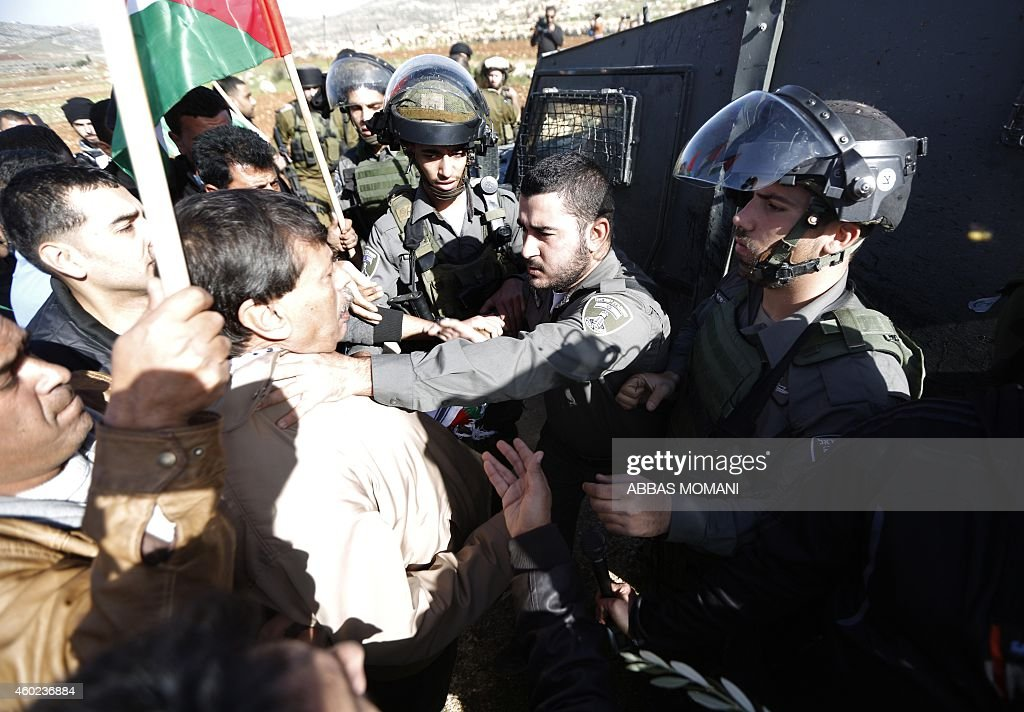An Israeli border guard grabs Palestinian official Ziad Abu Ein in charge of the issue of Israeli settlements for the Palestinian Authority during a...