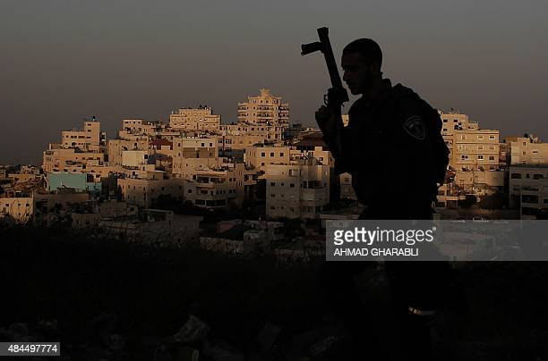 An Israeli border guard patrols in the east Jerusalem Arab neighbourhood of Issawiya on August 19 during clashes with Palestinian stonethrowers...