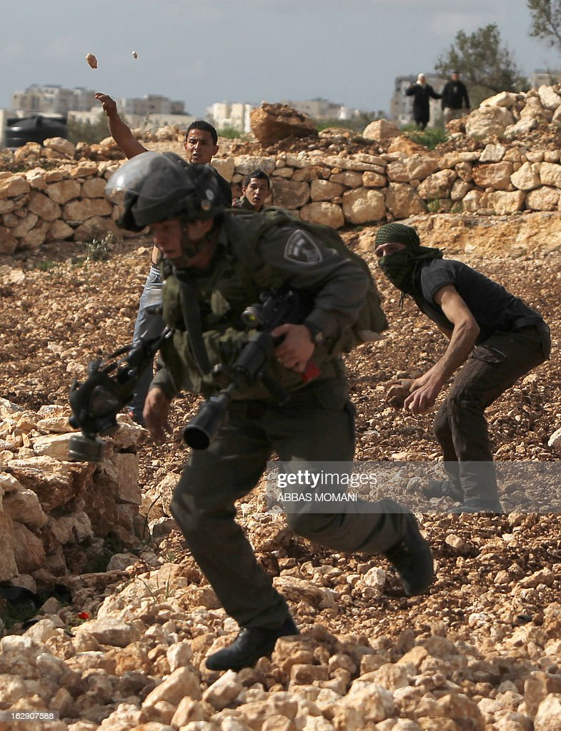 An Israeli border guard runs, as Palestinian youth throw stones at them during clashes between hundreds of youths and Israeli security in the West Bank village of Bilin on March 1, 2013, following a large march which headed towards Israel's controversial separation barrier in support of Palestinian prisoners held in Israeli jails, and marking eight years of weekly protests which kicked off in February 2005, against Israel's barrier which encroaches on Palestinian villagers' lands. AFP PHOTO/ABBAS MOMANI