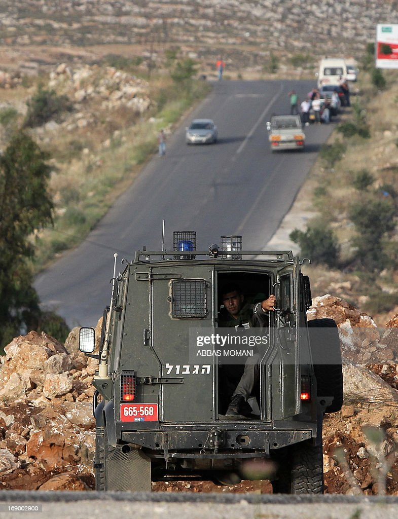 An Israeli border guard sits in the back of the vehicle in front of a makeshift roadblock leading to the village of Deir Jarir east of Ramallah on May 18, 2013. Israeli soldiers closed the road leading to Deir Jarir due to ongoing clashes with Palestinian demonstrators. AFP PHOTO/ABBAS MOMANI