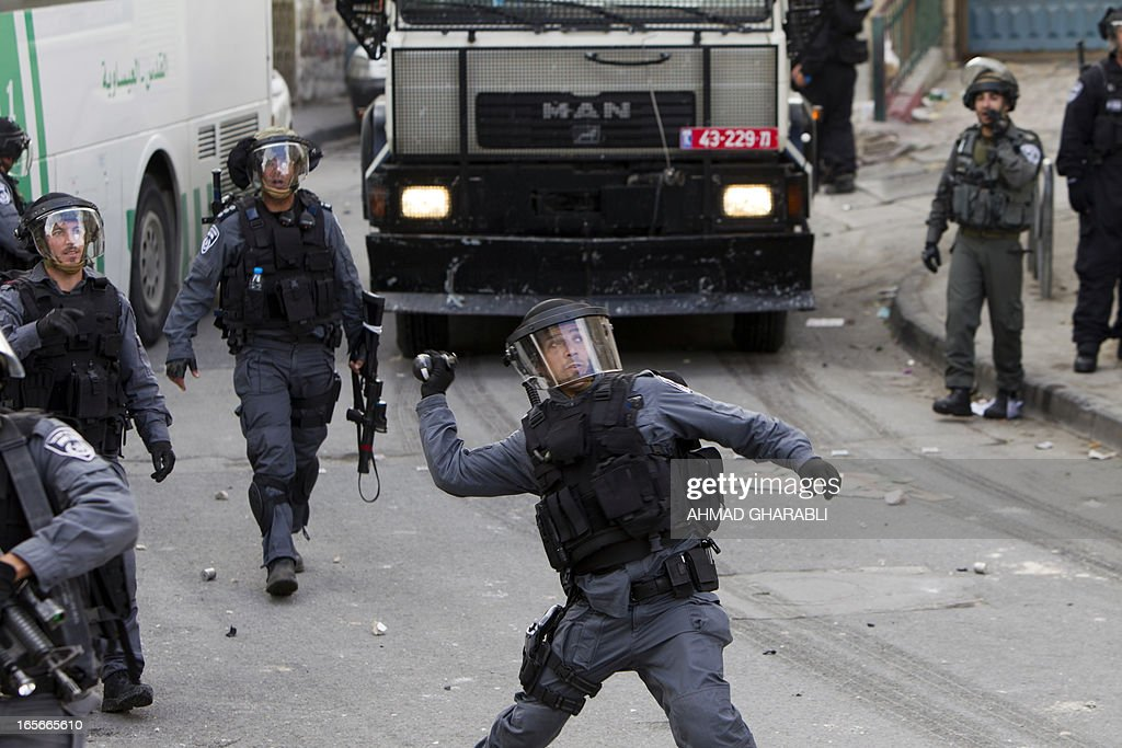 An Israeli border guard throws a smoke grenade during clashes with Palestinian protesters in the Issawiya district of Arab east Jerusalem on April 5, 2013. Israeli police dispersed Palestinian demonstrators after Muslim prayers in Jerusalem, making three arrests after days of violent protests around the West Bank, a spokeswoman said.